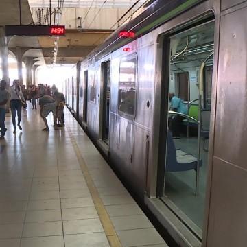 Homem em cadeira de rodas é carregado por passageiros em trilhos do metrô