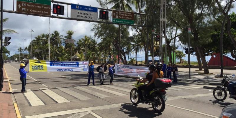 Arte-educadores estão nos dois lados da Avenida Boa Viagem com faixas alertando que o lixo nas ruas possibilita a reprodução do mosquito