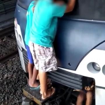 Meninos pegam carona do lado de fora de trem do metrô
